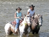 Leslie & Kris sitting on their horses in the Clarion River in PA.